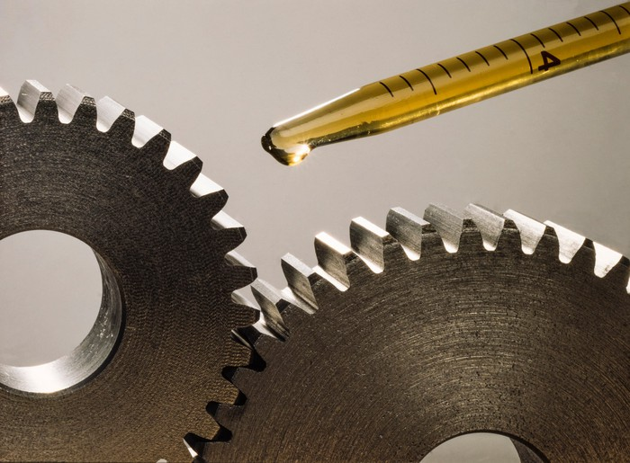 Two gears are lubricated with a drop of oil from a pipette.