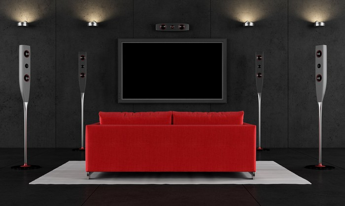 A home theater, with a large red couch in front of a giant screen.