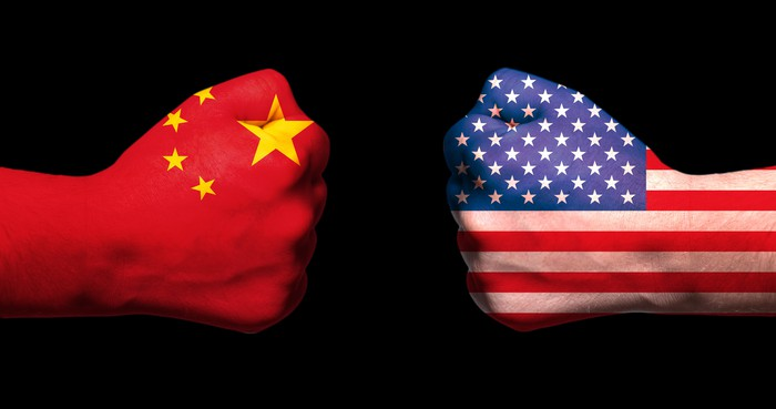 Two fists emblazoned with Chinese and American flags