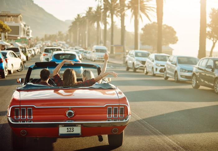 A red convertible on a road lined with palm trees, containing people waving their arms happily