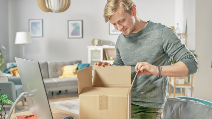 A man opening a package in front of a computer.