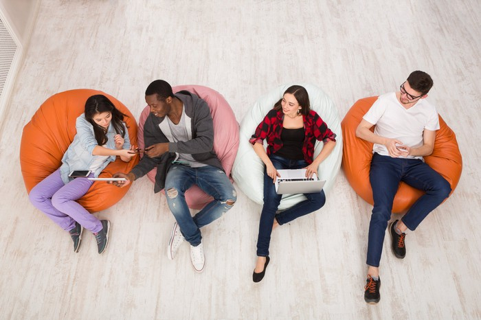 Overhead shot of four young people with phones and computers, sitting on beanbags