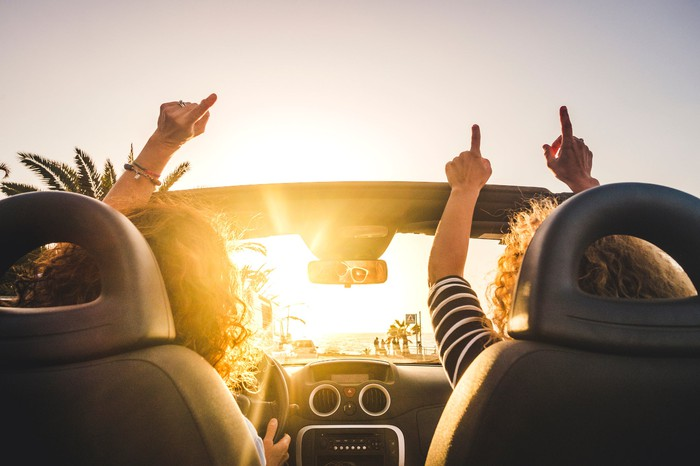 Two women driving in a convertible with their hands in the air while music is playing.