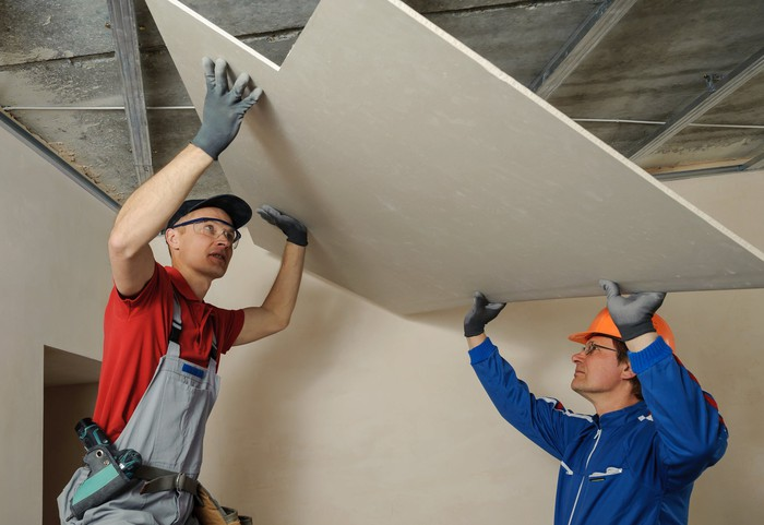 Two contractors installing drywall on the ceiling.