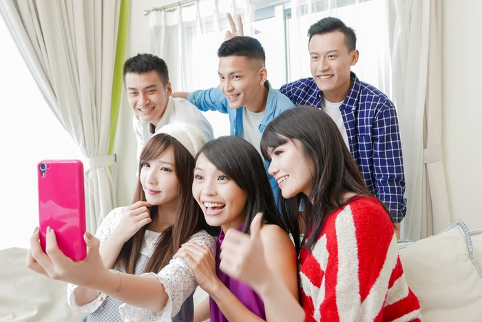A group of young adults take a selfie with a smartphone.
