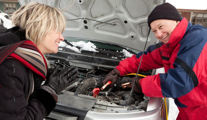 Man jump-starting car battery for woman