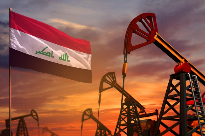 Oil pumps and an Iraqi flag with the sun setting in the background.