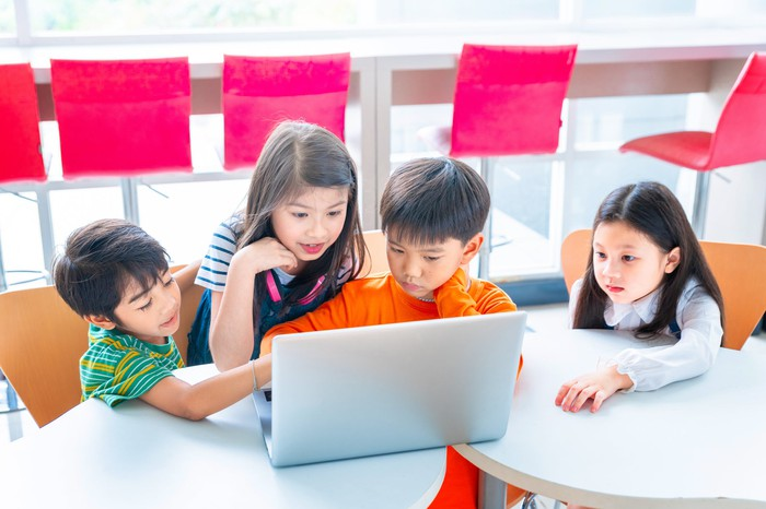 Four young children looking at a computer.