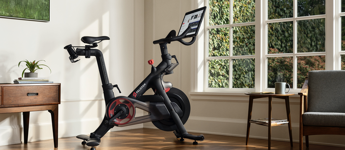 A Peloton exercise bike sitting in a living room of a house.