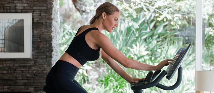 A woman using a Peloton bike.