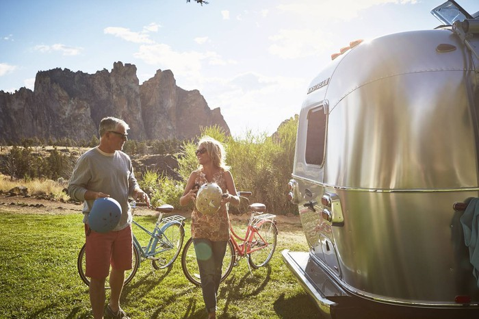 Happy family on a sunny day next to their stainless steel Airstream RV.