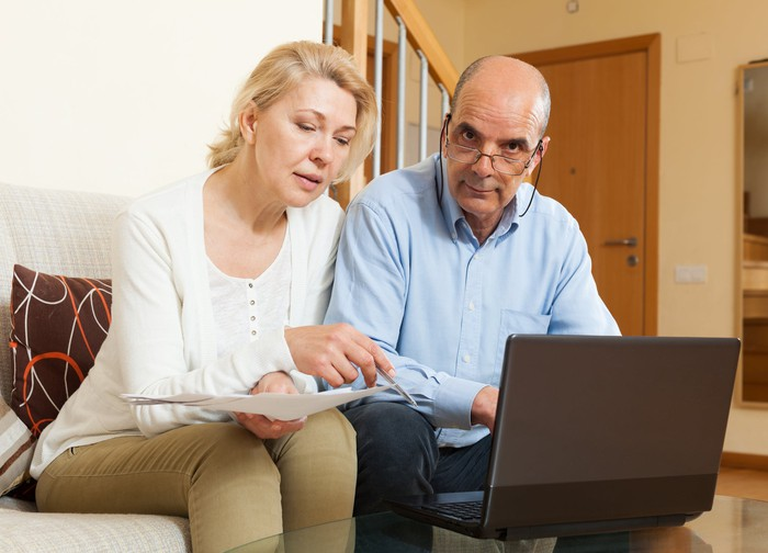 A mature couple sitting on a couch in front of a computer and reviewing their finances, with the husband looking particularly annoyed.
