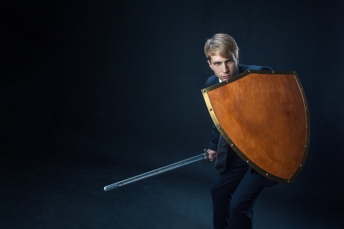 A professionally dressed man wielding a sword, taking a defensive stance behind his shield.