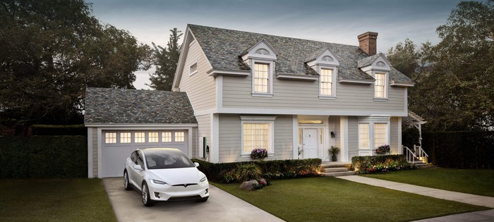 Home with a solar roof and a Tesla electric vehicle in the driveway.