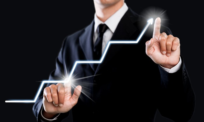 A man in a suit touches two illuminated points on an upward-trending line suggesting a rising stock chart.