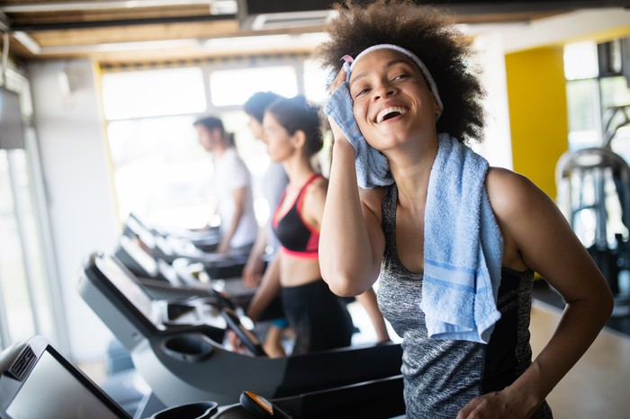 Woman on treadmill wiping herself with a towel