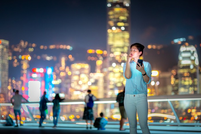 A young woman checks her smartphone at night.