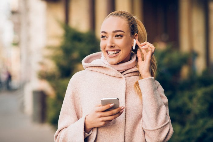 woman walking wearing airpods and holding iphone