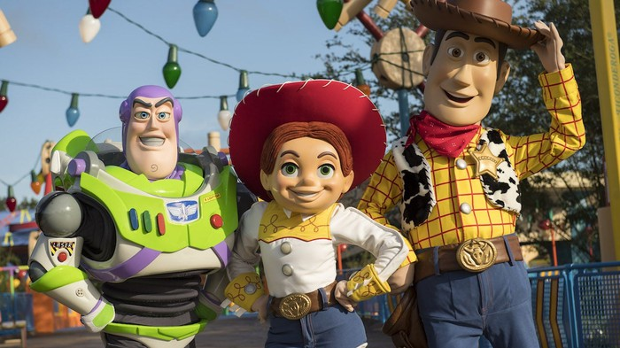 Costumed Woody, Jessie, and Buzz Lightyear characters at Disney World's Toy Story Land.
