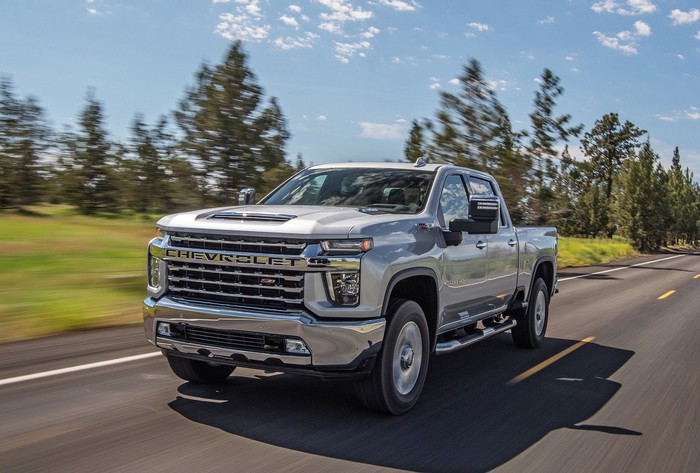 A silver 2020 Chevrolet Silverado HD, a heavy-duty pickup truck, driving along a road with trees in the background
