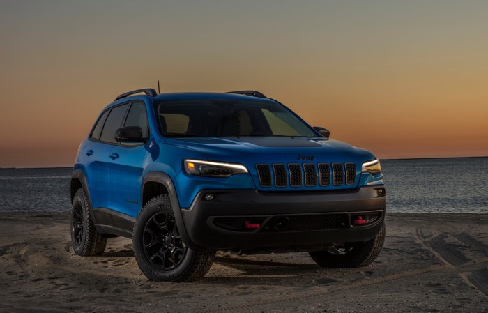 A blue 2019 Jeep Cherokee Trailhawk, parked on a beach at dusk