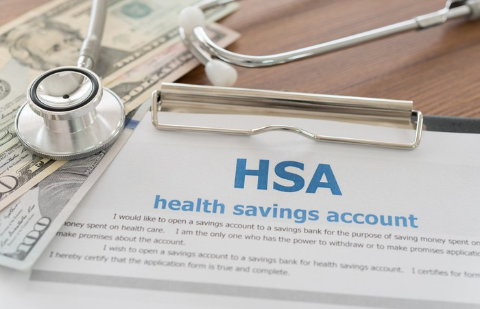 An HSA form on a clipboard, next to bills and a stethoscope