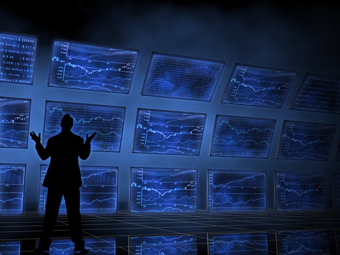 A silhouetted person in front of multiple blue-lit screens showing various charts and graphs