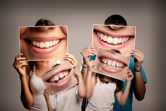 Man, woman, and two children holding pictures of smiles showing teeth in front of their faces