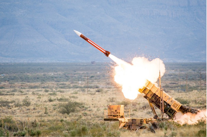 A Patriot missile rockets out of its launcher in a large, open field.