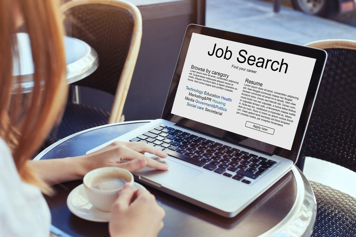 """A woman sits at a small table in a restaurant drinking coffee in front of a laptop computer that says """"Job Search"""""""