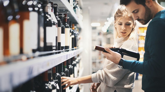 Photograph of young couple in liquor store looking at a bottle of wine.