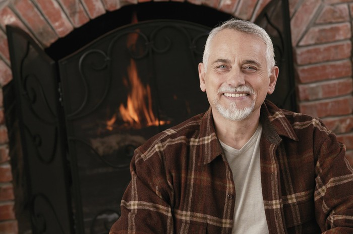 An older man smiling in front of a fireplace