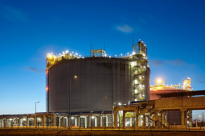 A natural gas storage tank surrounded by lights at dusk