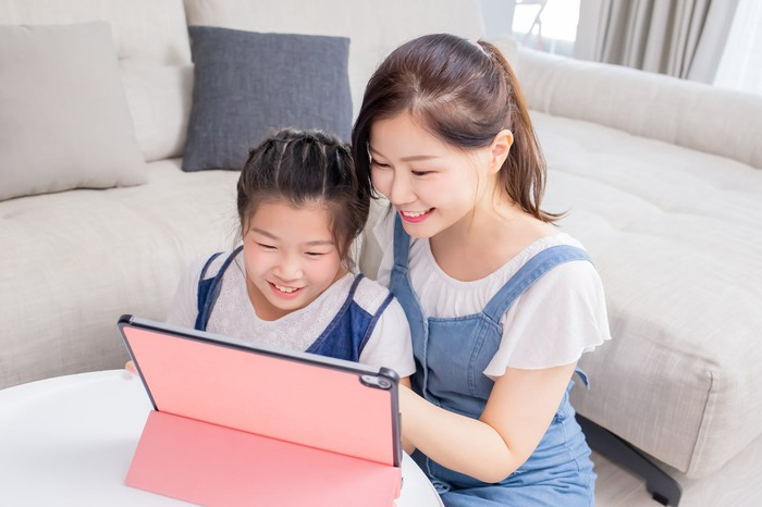 A woman and a young girl looking at a tablet.