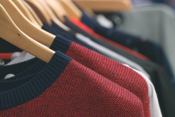 Navy and red shirts hang on hangers in a store.