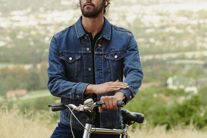 A man, standing next to a bicycle, wearing a Levi's trucker jacket.