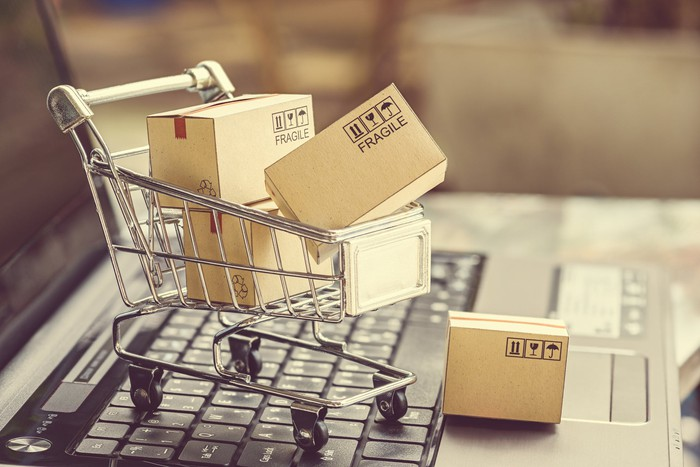 A miniaturized shopping cart full of boxes sitting on top a laptop, illustrating e-commerce.