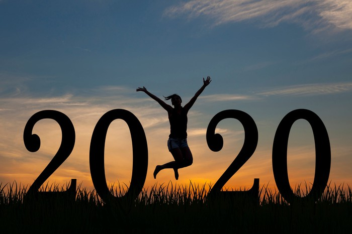A large sign that reads 2020 against a sunset with a woman jumping off the ground in between the two twenties.