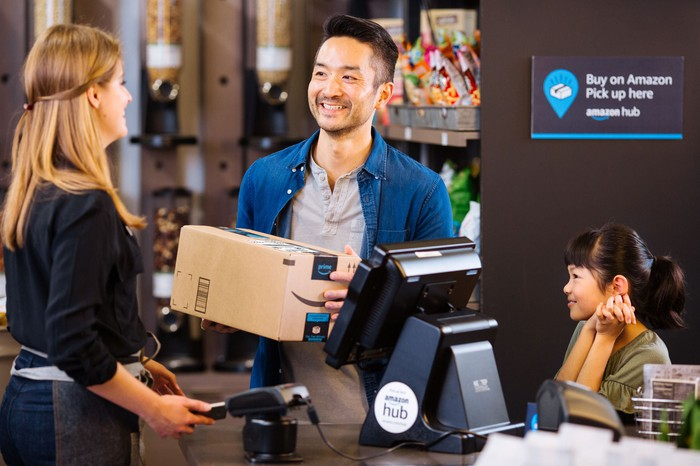 A man smiles as he picks up an Amazon package from a smiling store clerk.