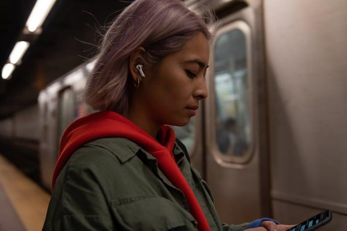 Une femme dans une station de métro avec AirPods Pro d'Apple.