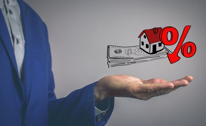 An illustration related to home sales where a hand holds up a drawing of a house on a pile of cash with a percentage sign next to it