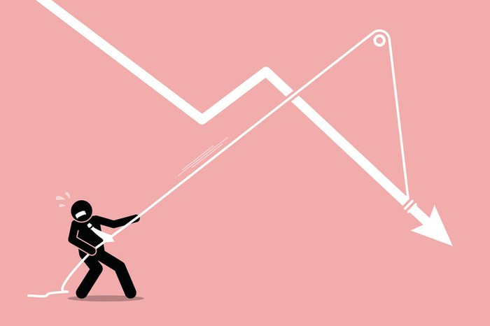 A stick figure businessman trying to pull a declining arrow into an upward trajectory.