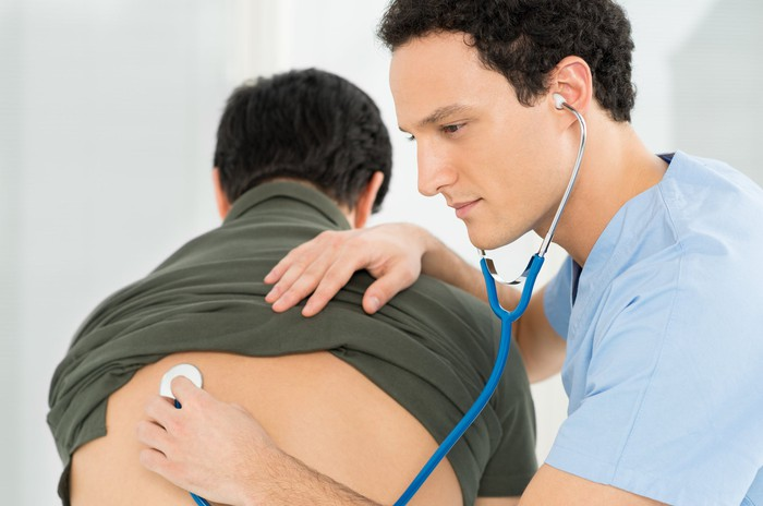 Man bends over while doctor places stethoscope on his back