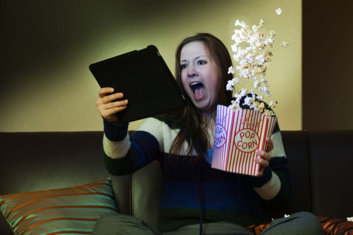 A surprised woman looking at a tablet, spilling a box of popcorn.