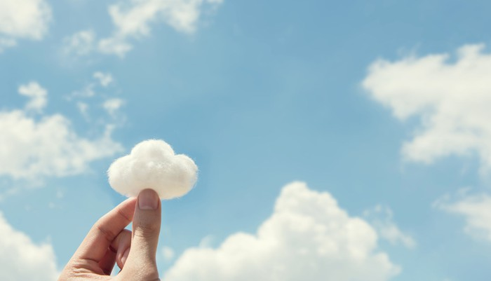 A hand holds a cloud-shaped cotton ball up to a sky filled with clouds.