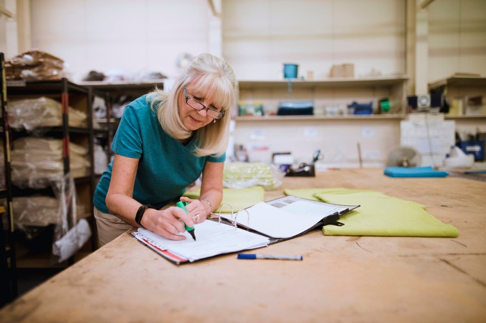Older woman doing paperwork in a factory