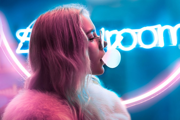 A young woman blows bubble gum in front of a neon sign.