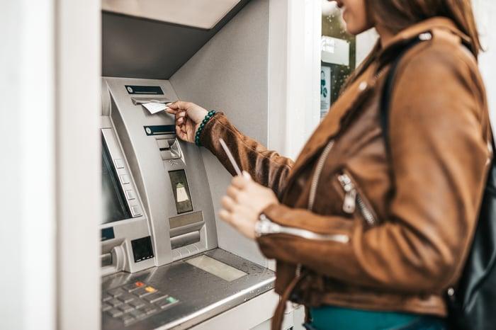 A woman using an ATM.