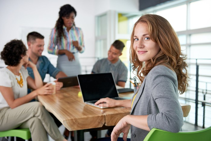 Business woman smiling with coworkers a a table talking.