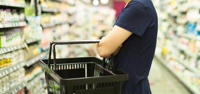 Customer holding shopping basket on a pharmacy aisle